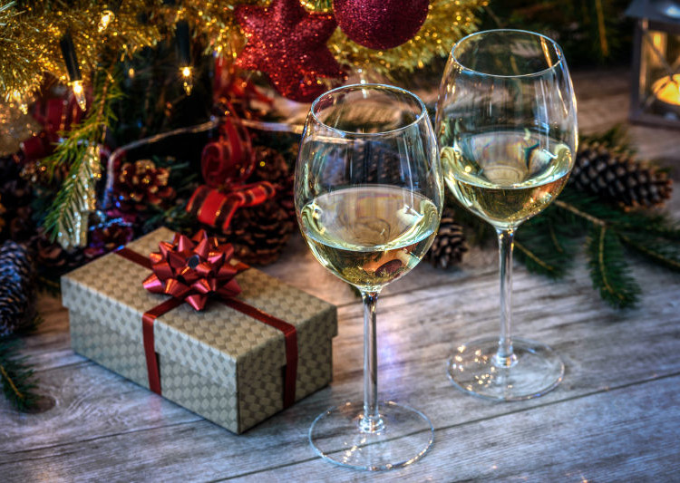 Two wineglas with white wine on a wooden table in the background of Christmas tree, gift and candles